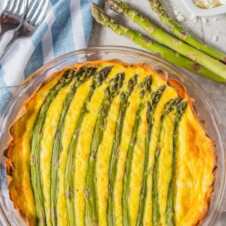 A whole asparagus quiche with fresh asparagus, feta cheese, and forks on the table.