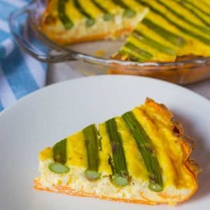Sweet potato asparagus quiche slice on a white plate with the whole quiche in the background