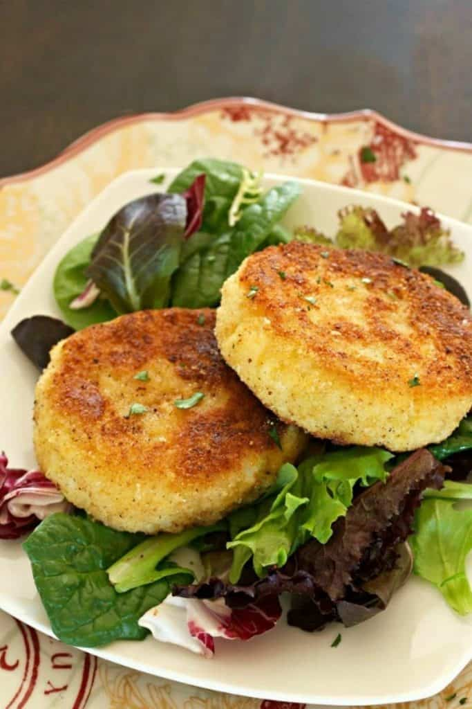 Two crispy risotto cakes on a bed of baby lettuces.
