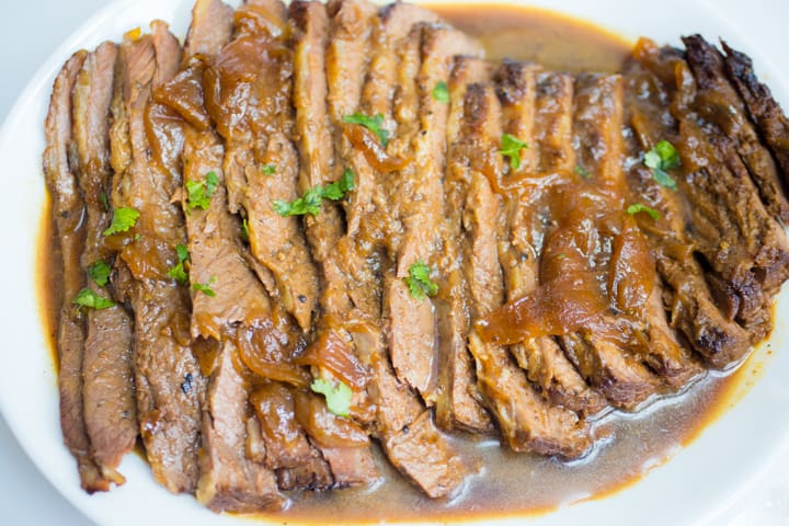 Sliced brisket topped with diced parsley on a white plate surrounded by an onion sauce.