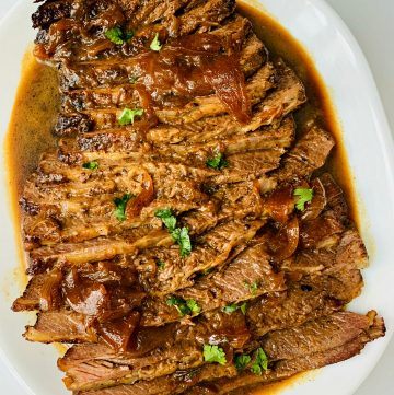 Braised Beef Brisket sliced and covered in an onion gravy with fresh chopped parsley sprinkled on top.