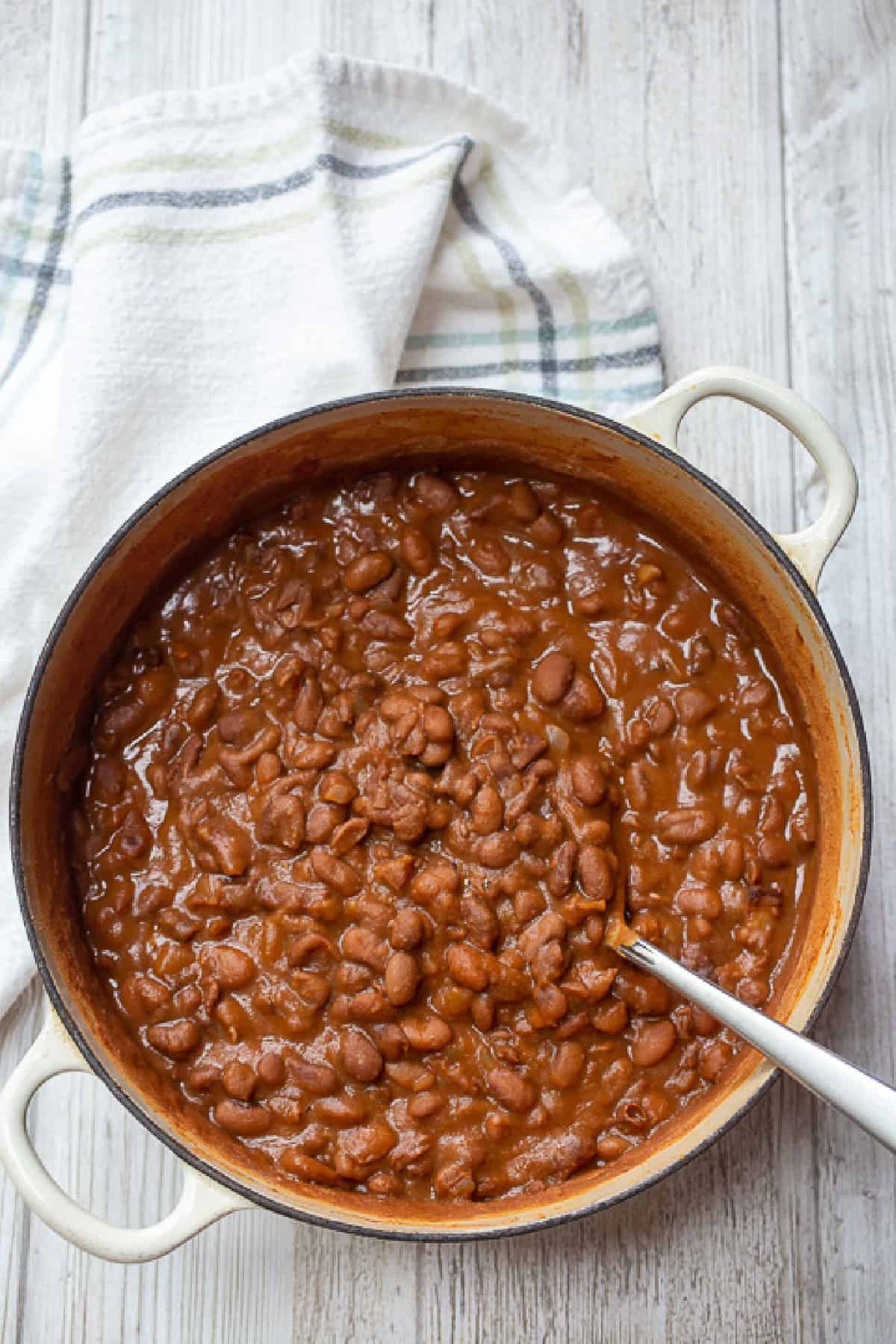 Cast iron pot of cooked easy baked beans recipe with a silver serving spoon sticking out and a white cloth towel with blue lines.